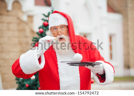 Portrait of senior man dressed as Santa Claus eating cookie against house - stock photo