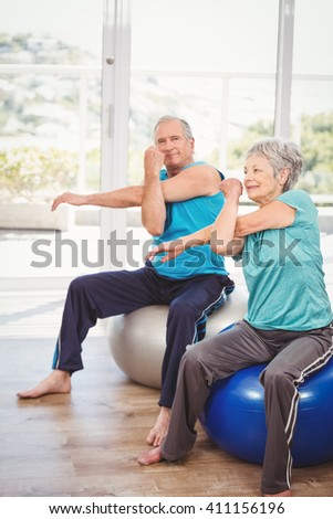 Portrait of senior man exercising with wife while sitting on exercise ball at home - stock photo