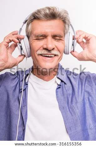 Portrait of senior man in headphones listening to music keeping eyes closed while standing against grey background.