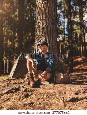 Portrait of senior man sitting alone by a tree with a tent in background. Mature man sitting at a campsite looking away on  summer day. - stock photo