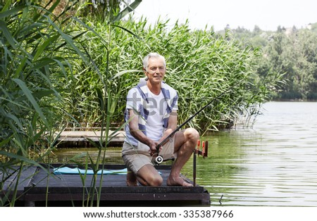 Portrait of senior man sitting at pier at the lakeside and fishing.
