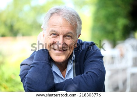 Portrait of senior man sitting in home garden - stock photo