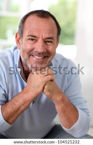 Portrait of senior man sitting in sofa at home - stock photo