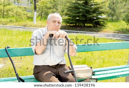 Portrait of senior man sitting on the bench park waiting for someone - stock photo