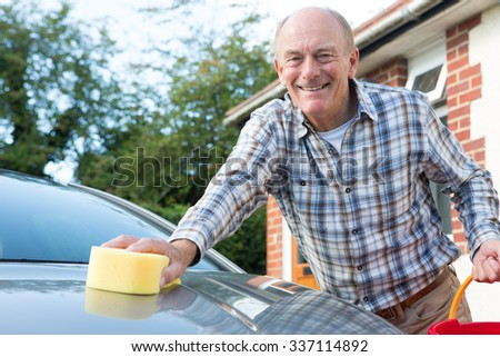 Portrait Of Senior Man Washing Car - stock photo