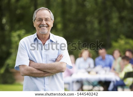 Portrait of senior man with arms crossed and family having lunch in background
