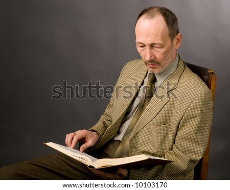 portrait of senior man with book on gray - stock photo