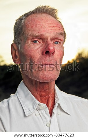 Portrait of senior man with white shirt standing in nature on hot summer day at sunset.