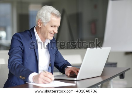 Portrait of senior managing director working on his laptop while sitting at office after business meeting. - stock photo