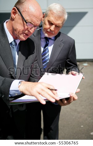 Portrait of senior men observing documents - stock photo