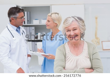Portrait of senior patient smiling while doctor and nurse discussing in background at clinic