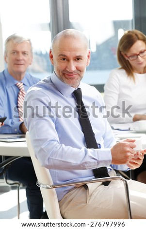 Portrait of senior sales man sitting at office while holding a cup of tea in his hands and relaxing. Business team working at background.  - stock photo