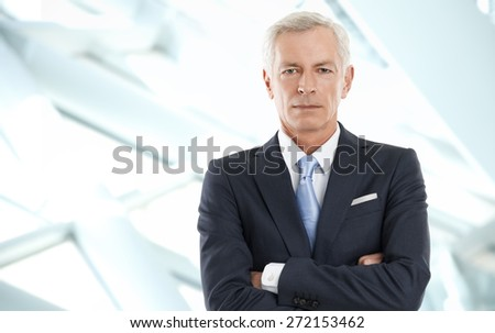 Portrait of senior sales man standing with arms crossed and looking at camera. Image of business person standing at office.
