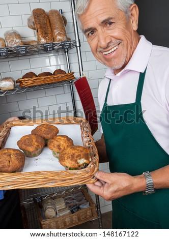 Portrait of senior salesman displaying tray of cupcakes at supermarket - stock photo