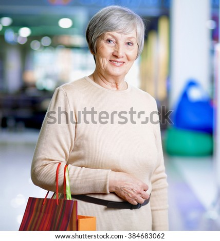 Portrait of senior smiling woman in shopping mall - stock photo