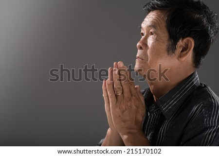 Portrait of senior Vietnamese man praying - stock photo
