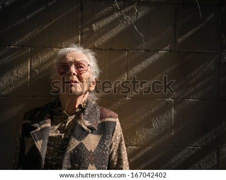 Portrait of senior woman against dramatic wall background. Closeup, copyspace. - stock photo