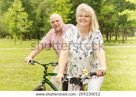 Portrait of senior woman and man ride bicycle outdoor. - stock photo