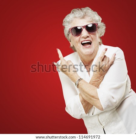 portrait of senior woman doing rock symbol over red background - stock photo