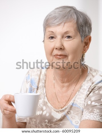 Portrait of senior woman drinking tea, looking at camera, smiling.?