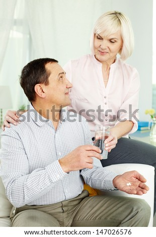 Portrait of senior woman giving a glass of water to her husband - stock photo