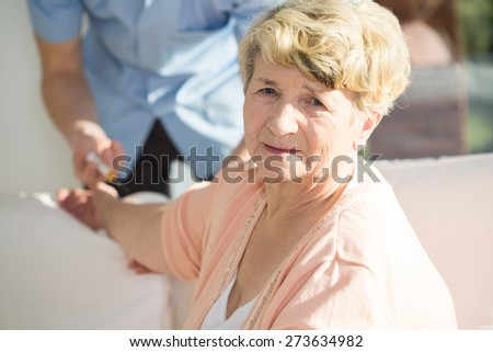 Portrait of senior woman having done an injection - stock photo