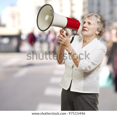 portrait of senior woman holding megaphone at city - stock photo
