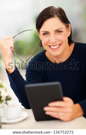 portrait of senior woman holding tablet computer - stock photo