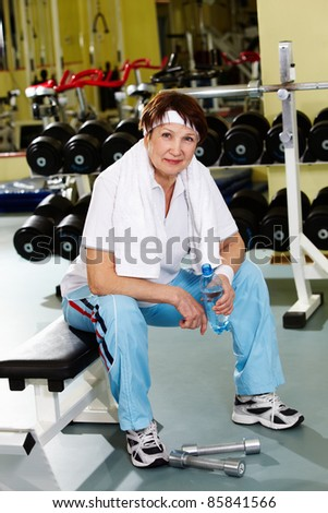 Portrait of senior woman in gym at break - stock photo