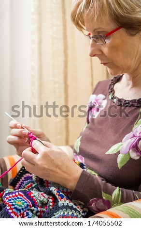 Portrait of senior woman knitting a vintage wool quilt with colorful patches