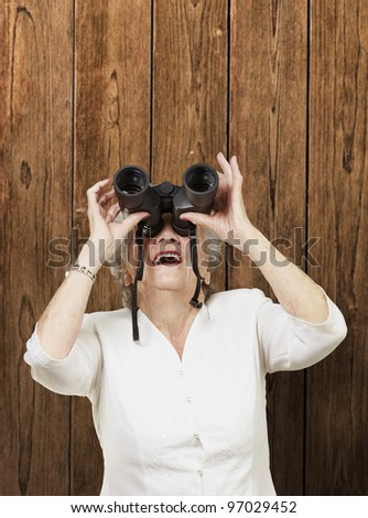 portrait of senior woman looking through a binoculars against a wooden wall - stock photo