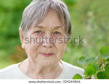 Portrait of senior woman outdoors in summer - stock photo