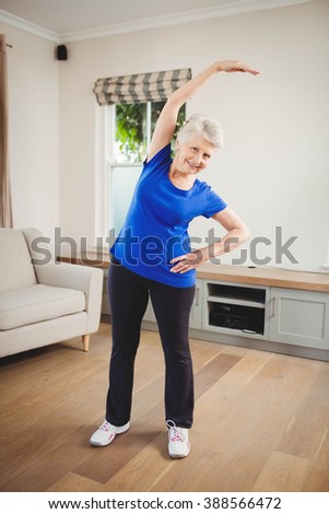 Portrait of senior woman performing stretching exercise at home - stock photo