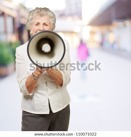 portrait of senior woman screaming with megaphone at city - stock photo