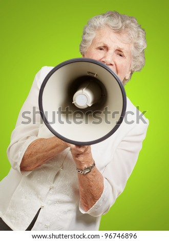 portrait of senior woman screaming with megaphone over green background - stock photo