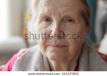 portrait of senior woman siting near the window - stock photo