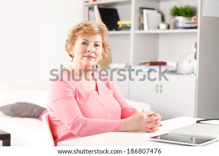 Portrait of senior woman sitting at desk. - stock photo