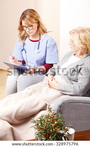 Portrait of senior woman sitting at home and consulting with middle age caregiver. Home healthcare nurse holding in her hand clipboard and giving advise while talking to elderly patient.