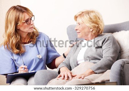 Portrait of senior woman sitting at home and consulting with middle age caregiver. Home healthcare nurse holding in her hand clipboard and giving advise while talking to elderly patient.  - stock photo