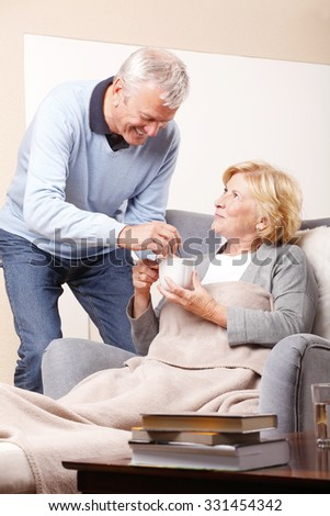 Portrait of senior woman sitting at home in armchair and old man giving medication and a glass of water to her.