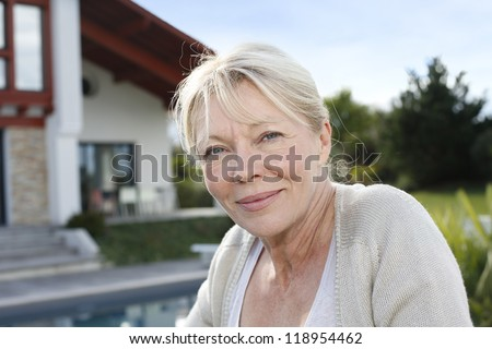Portrait of senior woman standing in front of home - stock photo