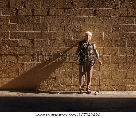 Portrait of senior woman standing near brick wall background. Copyspace.