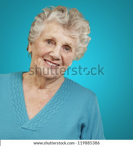 portrait of senior woman standing over blue background - stock photo