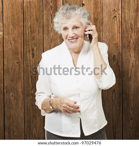portrait of senior woman talking on mobile against a wooden wall - stock photo