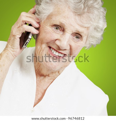 portrait of senior woman talking on mobile over green background - stock photo
