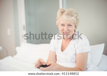 Portrait of senior woman using phone on bed at home - stock photo