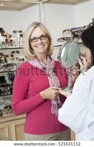 Portrait of senior woman wearing glasses while optician holding mirror