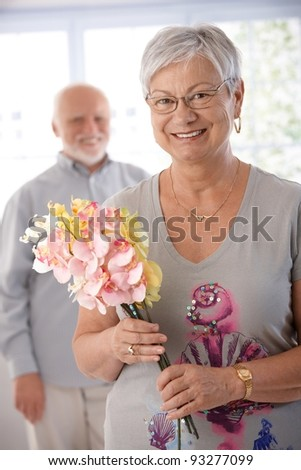Portrait of senior woman with bouquet, smiling. man at background.?