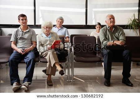 Portrait of senior woman with other people waiting for the doctor in hospital lobby - stock photo