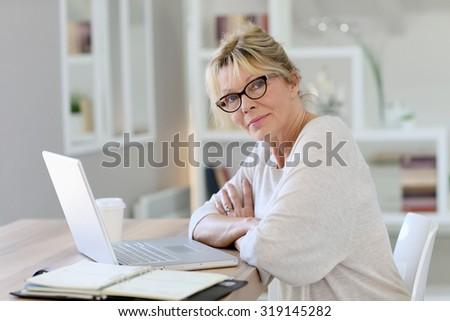 Portrait of senior woman working on laptop computer - stock photo